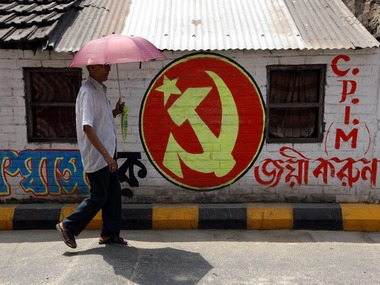 A man walks past Communist Party of India (Marxist) party symbol in Kolkata